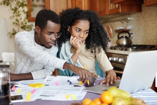 Afrykańska Rodzina Składająca Się Z Dwóch Osób Siedząca Przy Stole W Kuchni I Płacąca Rachunki Online Za Pomocą Laptopa: Mężczyzna W Okularach Wskazujący Palcem Wskazującym Na Ekran Notebooka, Wyjaśniający Coś Swojej żonie Darmowe Zdjęcia