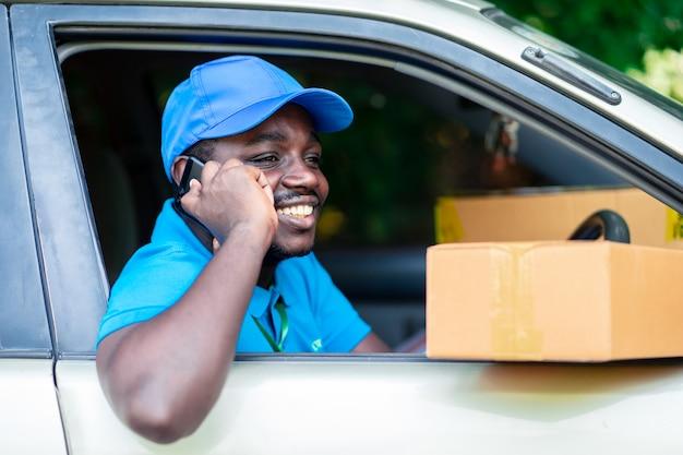 Afrykański doręczeniowy mężczyzna opowiada telefonem w samochodzie Premium Zdjęcia