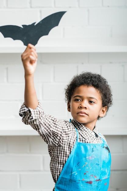 Afrykański Młodzieniec W Niebieskim Fartuchu Trzyma Ręcznie Robiony Symbol Halloween W Kształcie Czarnego Nietoperza W Uniesionej Ręce Premium Zdjęcia