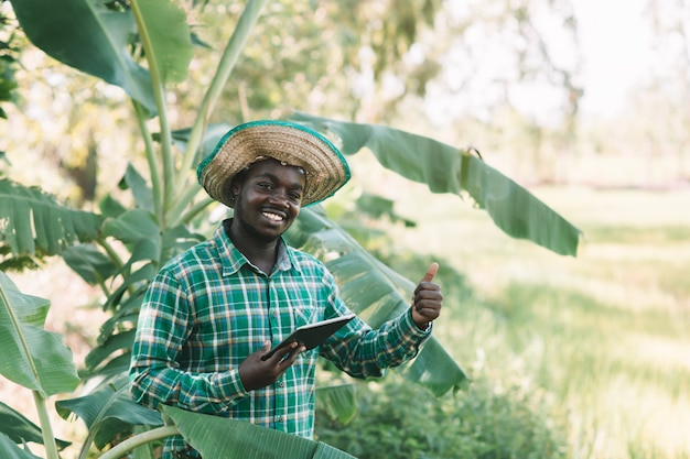 Afrykański średniorolny Mężczyzna Patrzeje Pastylkę Przy Organicznie Gospodarstwem Rolnym Premium Zdjęcia