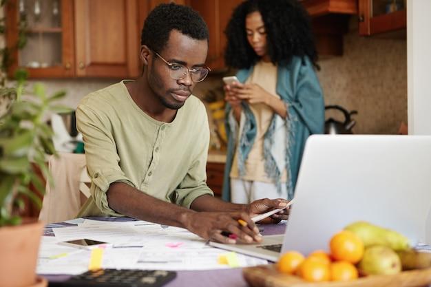Afrykańskie Małżeństwo W Obliczu Kłopotów Finansowych. Poważny Mężczyzna W Okularach Obliczający Wydatki Domowe Za Pomocą Laptopa, Siedzący Przy Kuchennym Stole Z Dużą Ilością Papierów. Budżet Rodzinny I Długi Darmowe Zdjęcia