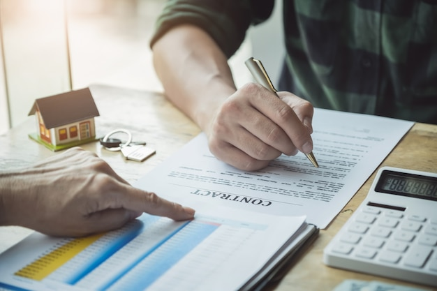 Agenci nieruchomości omawiający pożyczki i stopy procentowe na zakup domów Premium Zdjęcia