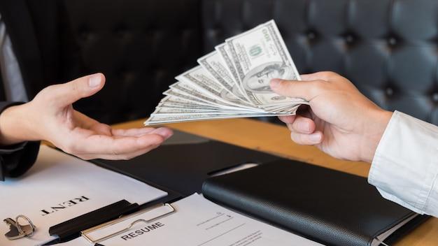 Agent deweloperski agent i podpisać dokument podając klucze nowego domu Premium Zdjęcia