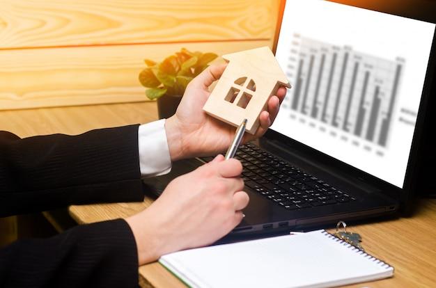 Agent nieruchomości posiada model domu, znaki wypełnia dokumenty siedzi za laptopa Premium Zdjęcia