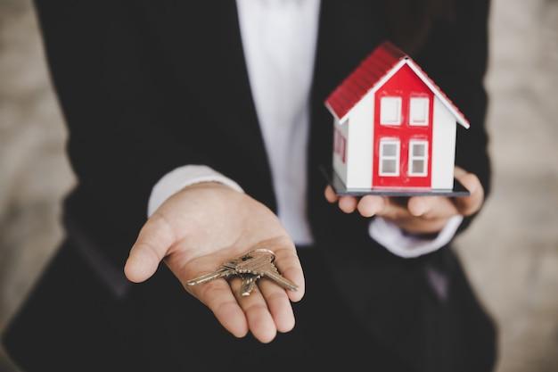 Agent nieruchomości z modelem domu i kluczami Premium Zdjęcia