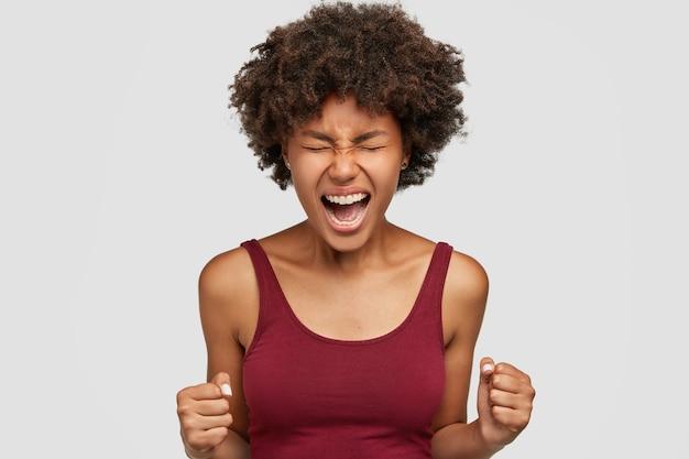 Agresywna Czarna Kobieta Z Fryzurą W Stylu Afro, Gniewnie Zaciska Pięści, Czuje Się Szalona I Zdesperowana, Trzyma Ręce Z Przodu, Gotowa Do Walki Lub Wyzwania Darmowe Zdjęcia