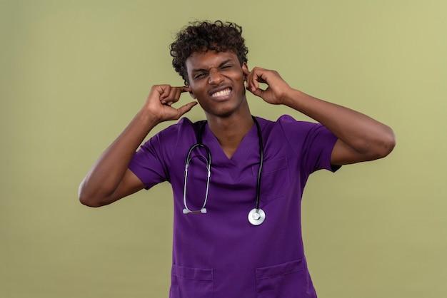 Agresywny Młody Przystojny Ciemnoskóry Lekarz Z Kręconymi Włosami W Fioletowym Mundurze Ze Stetoskopem Trzymającym Ręce Na Uszach Na Zielonej Przestrzeni Darmowe Zdjęcia