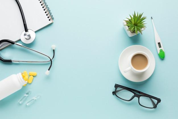 Akcesoria medyczne; filiżanka kawy i okulary na niebieskim tle Darmowe Zdjęcia