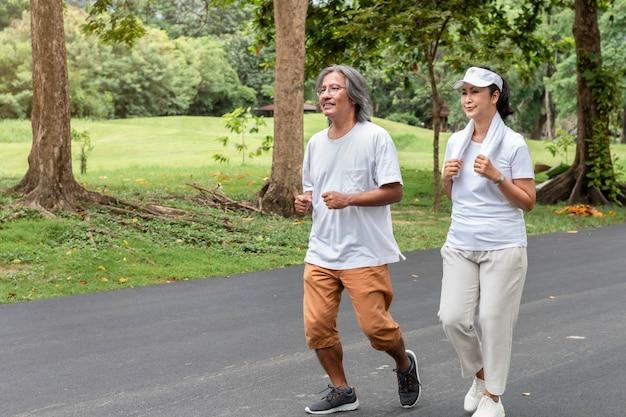 Aktywny Azjatycki Para Senior W Sportswear Jogging Przy Parkiem. Premium Zdjęcia