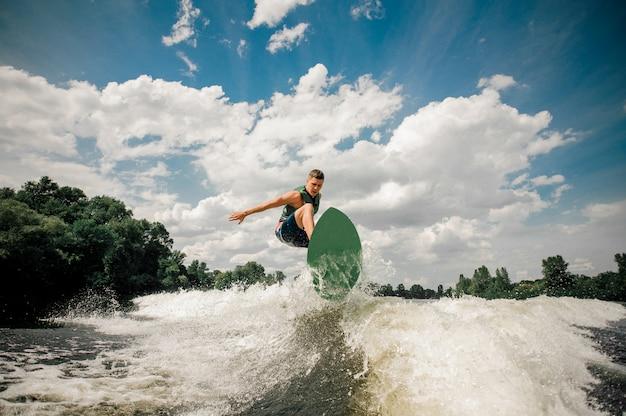 Aktywny Człowiek Wakesurfing Na Desce W Dół Rzeki Na Tle Pochmurnego Nieba I Drzew Premium Zdjęcia