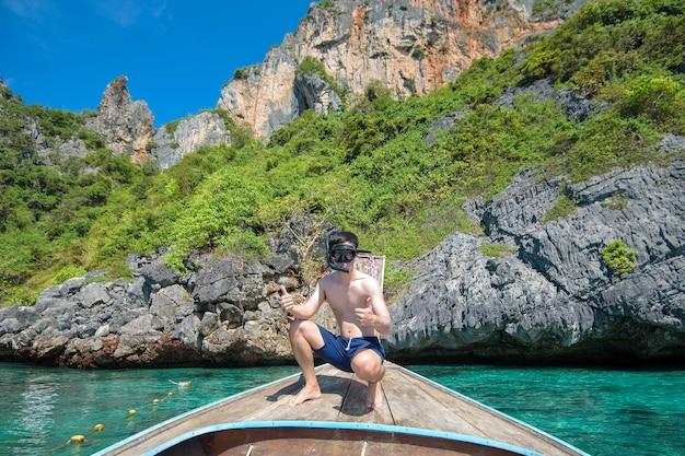 Aktywny Mężczyzna Na Tradycyjnej Tajlandzkiej łodzi Typu Longtail Jest Gotowy Do Snorkelingu I Nurkowania, Wyspy Phi Phi, Tajlandia Premium Zdjęcia