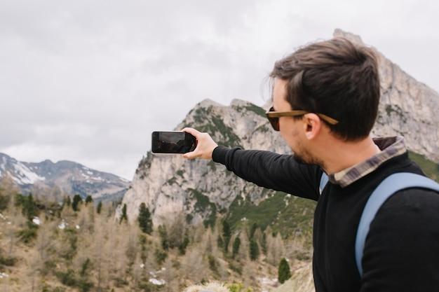 Aktywny Młody Człowiek Z Ciemnobrązowymi Włosami W Koszuli Pod Czarnym Swetrem, Podróżujący Po Górach I Nagrany Wideo Na Smartfonie Darmowe Zdjęcia