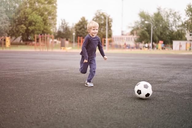 Aktywny Tryb życia W Nowoczesnym Mieście - Mały Chłopiec Bawi Się Piłką Nożną Na Stadionie Premium Zdjęcia