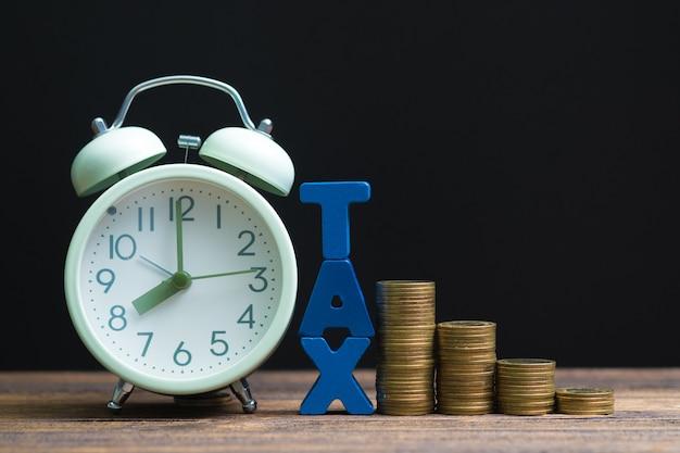 Alfabet podatkowy ze stosem monet i vintage budzik Premium Zdjęcia