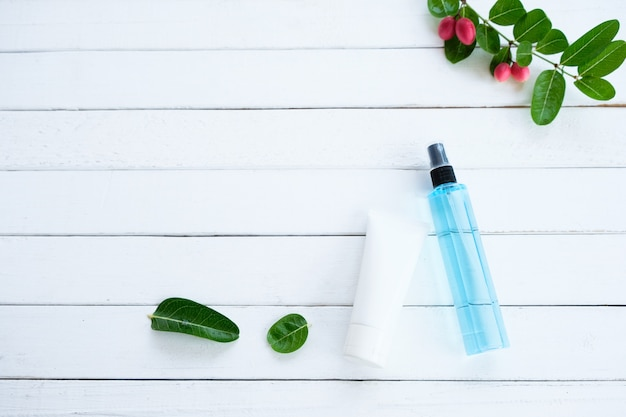 Alkohol Niebieski I żelowy Do Czyszczenia Rąk, Umieszczony Na Białej Drewnianej Podłodze Z Zielonymi Liśćmi. Premium Zdjęcia