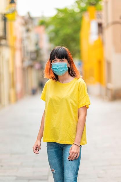 Alternatywny Kaukaski Model Z Pomarańczowymi Włosami, Ubrany W żółtą Koszulę I Maskę Na środku Ulicy. Premium Zdjęcia