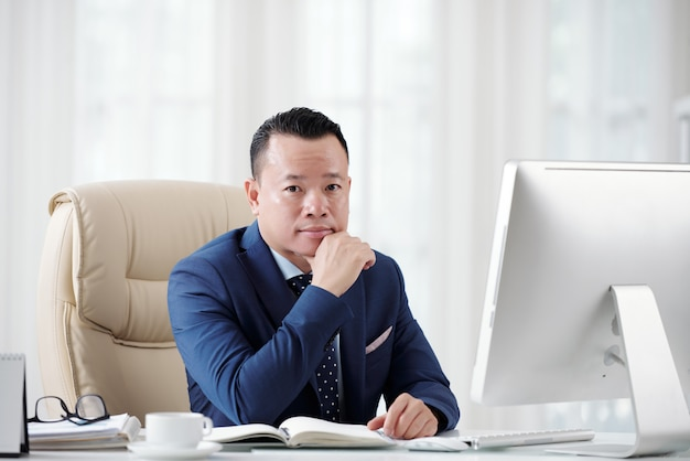 Ambitny biznesmen planuje swoją przyszłą karierę siedzi przy biurowym stołem Darmowe Zdjęcia