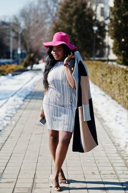 Amerykanin Afrykańskiego Pochodzenia Kobieta Przy Kapeluszem I żakietem Z Telefonu Odprowadzeniem Przy Ulicami. Premium Zdjęcia