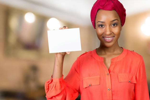 Amerykanin afrykańskiego pochodzenia kobieta trzyma pustego papier Premium Zdjęcia