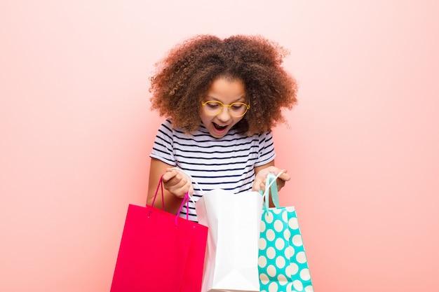 Amerykanin Afrykańskiego Pochodzenia Mała Dziewczynka Przeciw Płaskiej ścianie Z Torba Na Zakupy Premium Zdjęcia