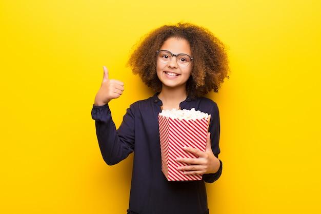 Amerykanin Afrykańskiego Pochodzenia Mała Dziewczynka Trzyma Popcorns Wiadro Przeciw Płaskiej ścianie Premium Zdjęcia