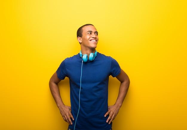 Amerykanin afrykańskiego pochodzenia mężczyzna z błękitną koszulką na żółtym tle pozuje z rękami przy modnym i roześmianym Premium Zdjęcia