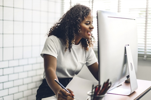 Amerykanin Afrykańskiego Pochodzenia Murzynka Pracuje Z Laptopem. Kreatywni Ludzie Biznesu Planują I Używają Pióra W Nowoczesnym Lofcie Premium Zdjęcia