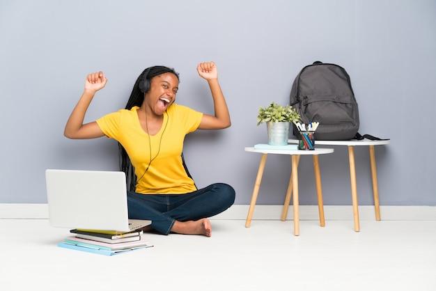 Amerykanin afrykańskiego pochodzenia nastolatka studencka dziewczyna z długim splatającym włosianym obsiadaniem na podłoga i tanu Premium Zdjęcia