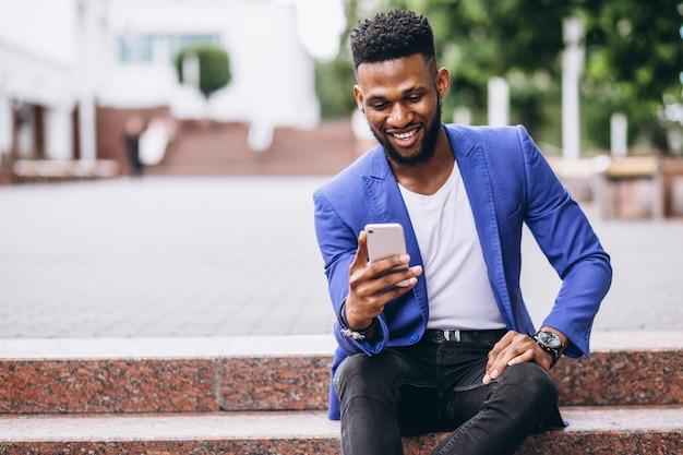 Amerykanina afrykańskiego pochodzenia mężczyzna w niebieskiej marynarce używać telefon Darmowe Zdjęcia