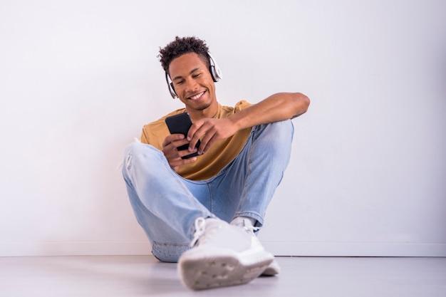 Amerykanina Afrykańskiego Pochodzenia Millennial Mężczyzna Texting Z Smartphone Premium Zdjęcia