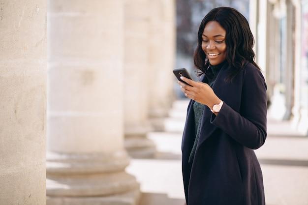 Amerykanina afrykańskiego pochodzenia studencka dziewczyna z telefonem uniwersytetem Darmowe Zdjęcia