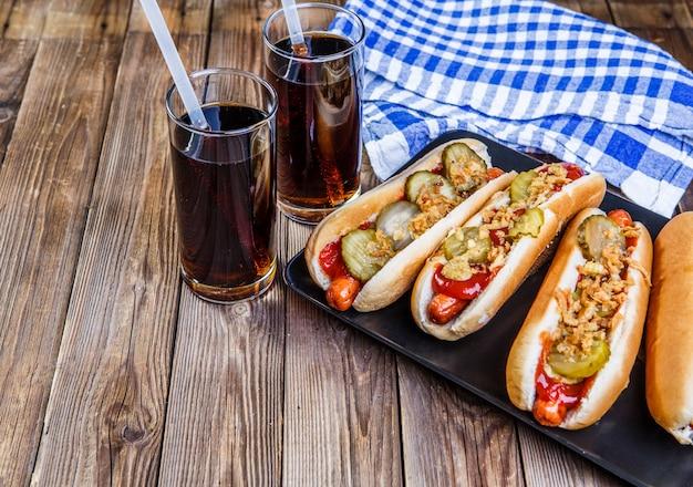 Amerykański hot dog z marynatami, cebulą, ketchupem, musztardą i dwoma napojami gazowanymi Premium Zdjęcia