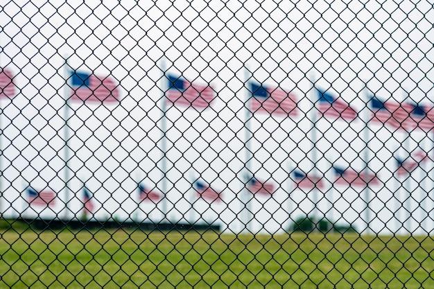 Amerykańskie Flagi Przy Waszyngtońskim Pomnikiem Za Drucianym Ogrodzeniem. Skoncentruj Się Na Ogrodzeniu Z Drutu Premium Zdjęcia