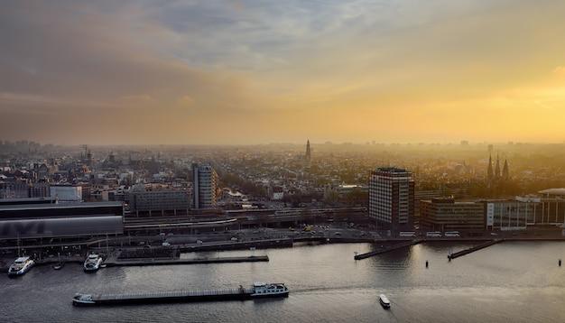 Amsterdam Gród Widok Z Góry O Zachodzie Słońca. Rzeka Ze Statkami, łodziami, Dworzec Centralny. Zwiedzanie Holenderskiego. Premium Zdjęcia