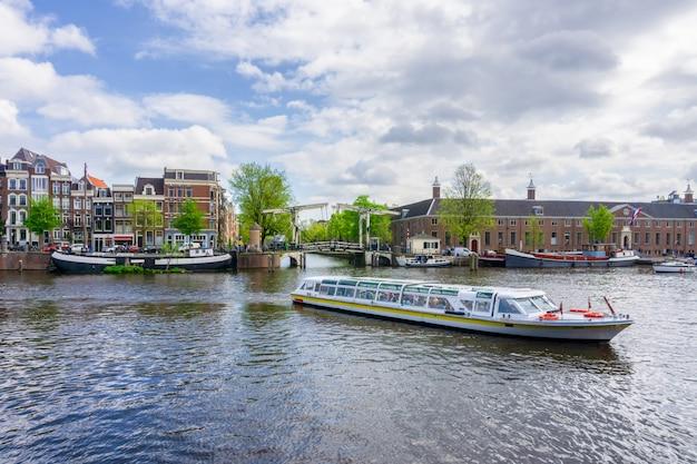 Amsterdam Holandie Tanczy Domy Nad Rzecznym Amstel Punktem Zwrotnym W Starym Europejskim Miasto Wiosny Krajobrazie Premium Zdjęcia