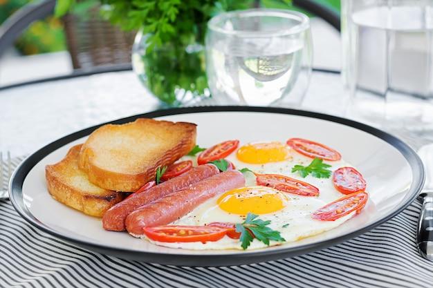 Angielskie śniadanie na letnim tarasie: jajka sadzone, kiełbasa, pomidory i tosty. kubek kawy. zamyka śniadanie hotelowy śniadanie. Premium Zdjęcia