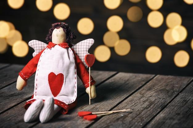 Anioł miękka zabawka z kierowym obsiadaniem na starym drewnianym tle. koncepcja valentine Premium Zdjęcia