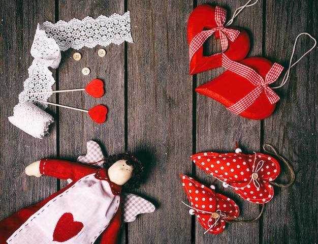 Anioł miękka zabawka z sercem, koronkową wstążką, guzikami i trzema czerwonymi sercami na starym drewnianym tle. koncepcja valentine. widok z góry. Premium Zdjęcia