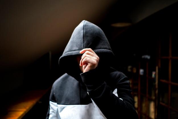 Anonimowy mężczyzna w ciemnym kapturze stojący w tajemniczej pozie Premium Zdjęcia
