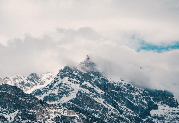 Antena Strzał Piękne Skaliste śnieżne Góry Zakrywać W Chmurach Darmowe Zdjęcia