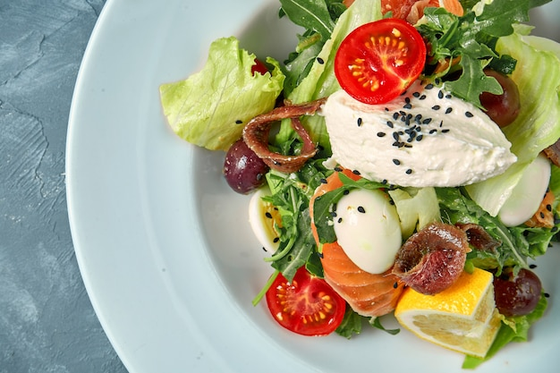 Apetyczna Sałatka Z Pomidorami, łososiem, Anchois I Twarożkiem W Białym Talerzu Na Betonie Premium Zdjęcia