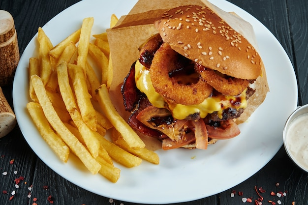 Apetyczny I Soczysty Burger Ze Smażoną Cebulą, Serem, Pomidorami I Kotletem Wołowym Na Białym Talerzu Z Frytkami. Widok Z Góry, Selektywne Focus Premium Zdjęcia