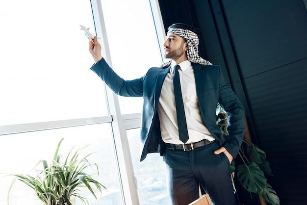 Arabska biznesmen pozycja przy okno z wzorcowym samolotem. Premium Zdjęcia