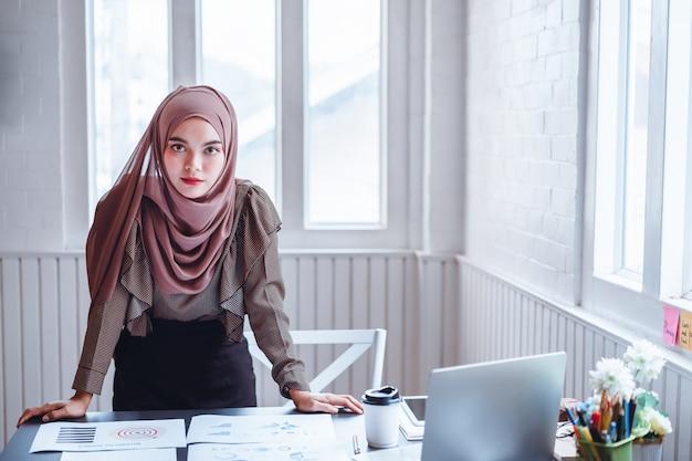 Arabska biznesowa kobieta w brown hijab przy biurowym miejscem pracy. Premium Zdjęcia