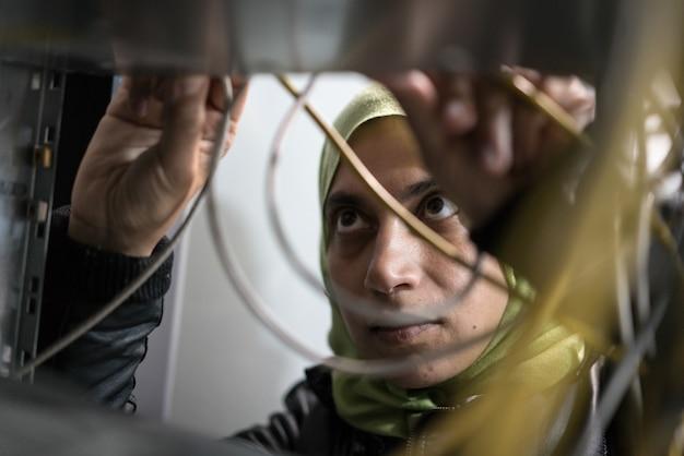 Arabska kobieta w serwerowni przełącza kable Premium Zdjęcia