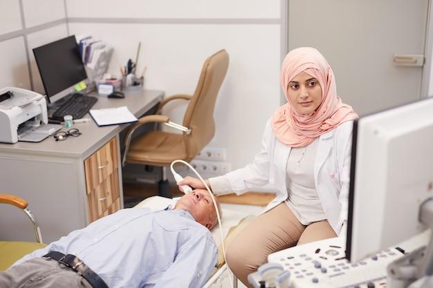 Arabska Pielęgniarka Bada Pacjenta Seniorów Premium Zdjęcia