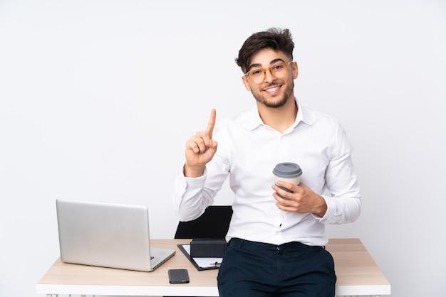 Arabski Mężczyzna W Biurze Na Białym Tle Pokazując I Podnosząc Palec Na Znak Najlepszych Premium Zdjęcia