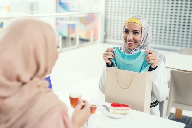 Arabskie Kobiety Siedzą W Kawiarni W Nowoczesnym Centrum Handlowym. Premium Zdjęcia