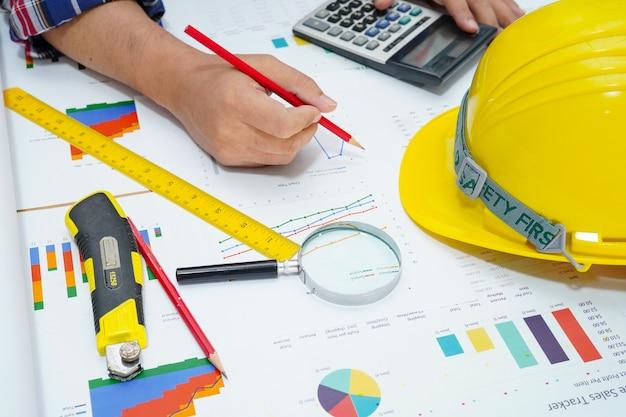 Architekt działający księgowość projektu z wykresem. Premium Zdjęcia