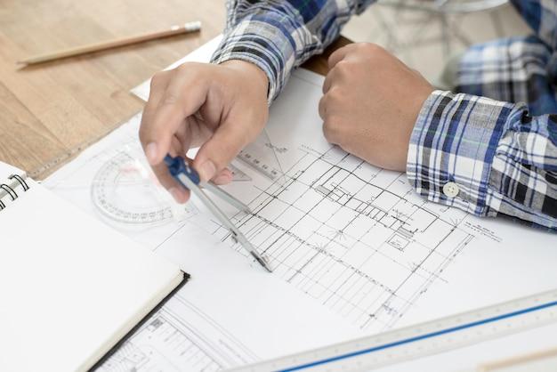 Architekt pracujący nad planem. przypadkowy mężczyzna pracuje na projekcie i architekturze modeluje z ołówkiem przy biurem. Premium Zdjęcia